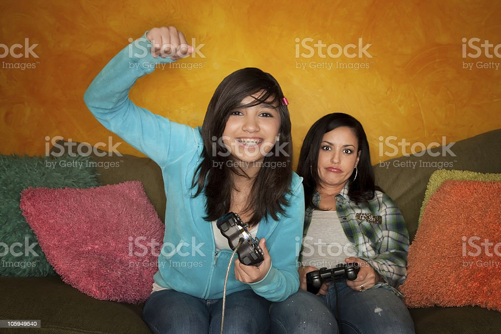 Hispanic Woman and Girl Playing Video game stock photo