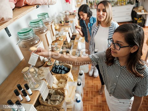 A hispanic everyday woman and two girls looking at eco-friendly products in a sustainable shop.