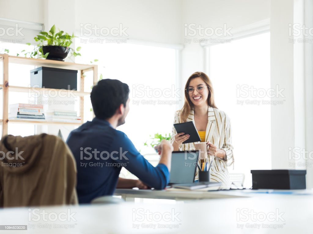 Hispanic woman and man working in and office stock photo