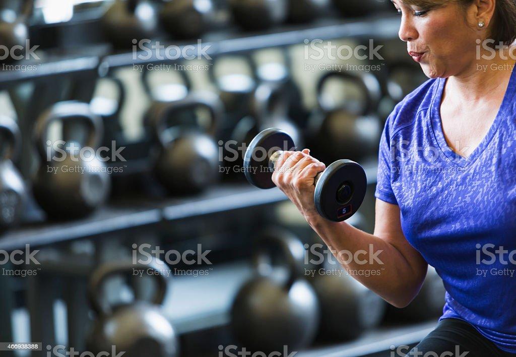 Hispanic woman at gym lifting dumbbell stock photo