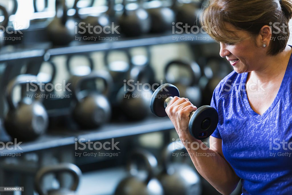 Hispanic woman at gym lifting dumbbell stock photo