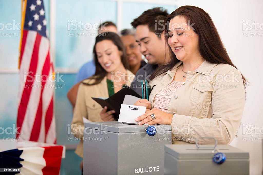 Hispanic woman casts ballot. November USA election. Voters background. stock photo
