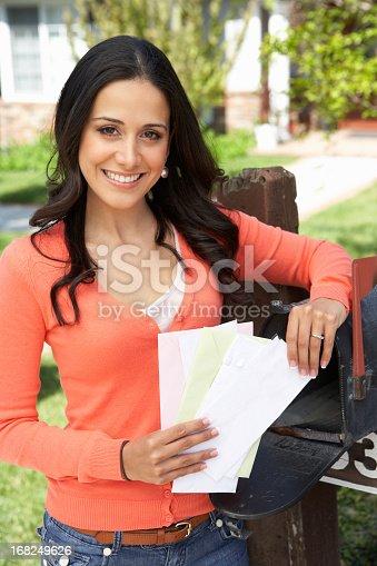 istock Hispanic Woman Checking Mailbox 168249626