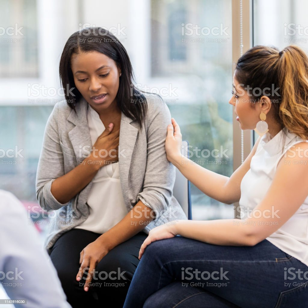 During group therapy, a mid adult Hispanic woman consoles her friend.