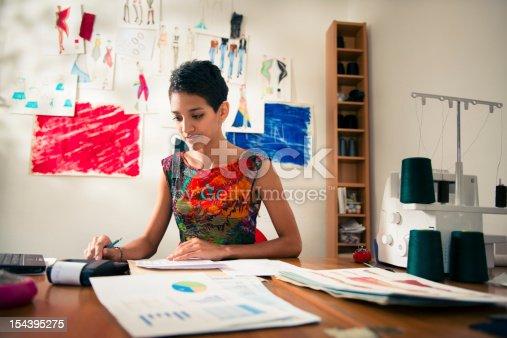istock hispanic woman doing budget in fashion designer atelier 154395275
