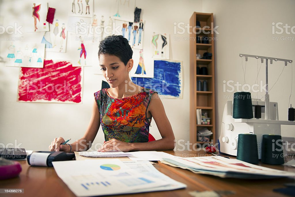 hispanic woman doing budget in fashion designer atelier stock photo