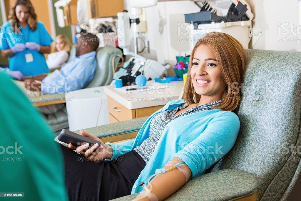 Hispanic woman donating blood in busy hospital donation bank stock photo