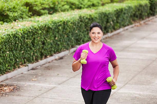 Hispanic woman exercising in park stock photo