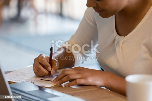 An unrecognizable Hispanic woman references the information on her laptop to fill out a job application at the coffee shop.