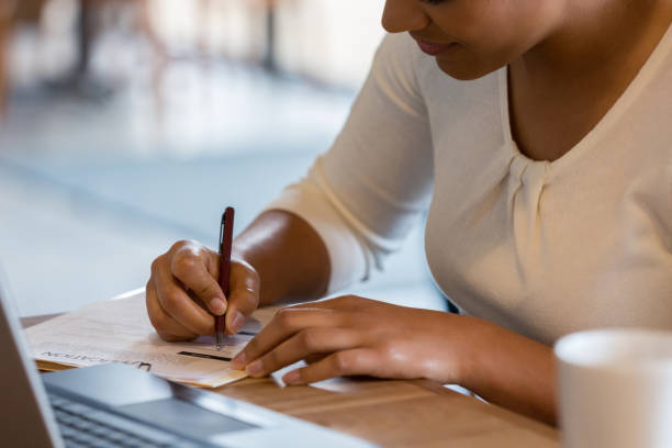 Hispanic woman fills out job application at coffee shop An unrecognizable Hispanic woman references the information on her laptop to fill out a job application at the coffee shop. application form stock pictures, royalty-free photos & images