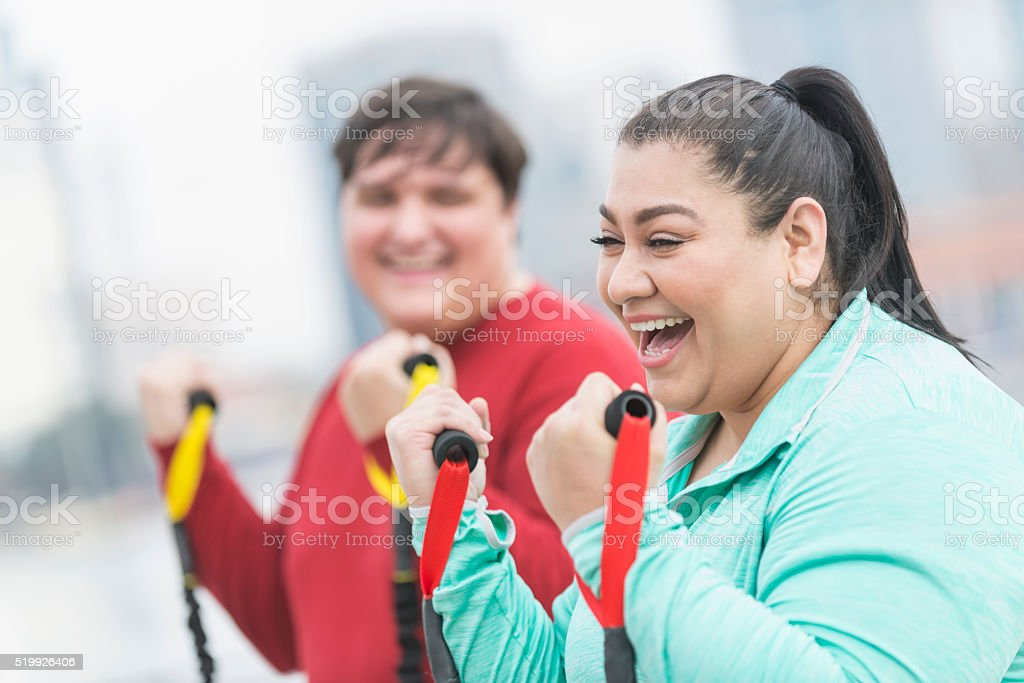 Hispanic woman, friend exercising with resistance bands stock photo