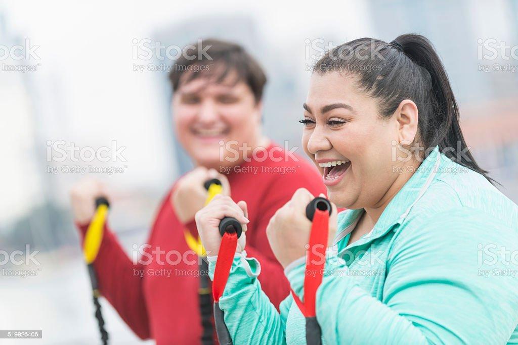 Mujer hispana, amigo ejercicio con bandas de resistencia - foto de stock
