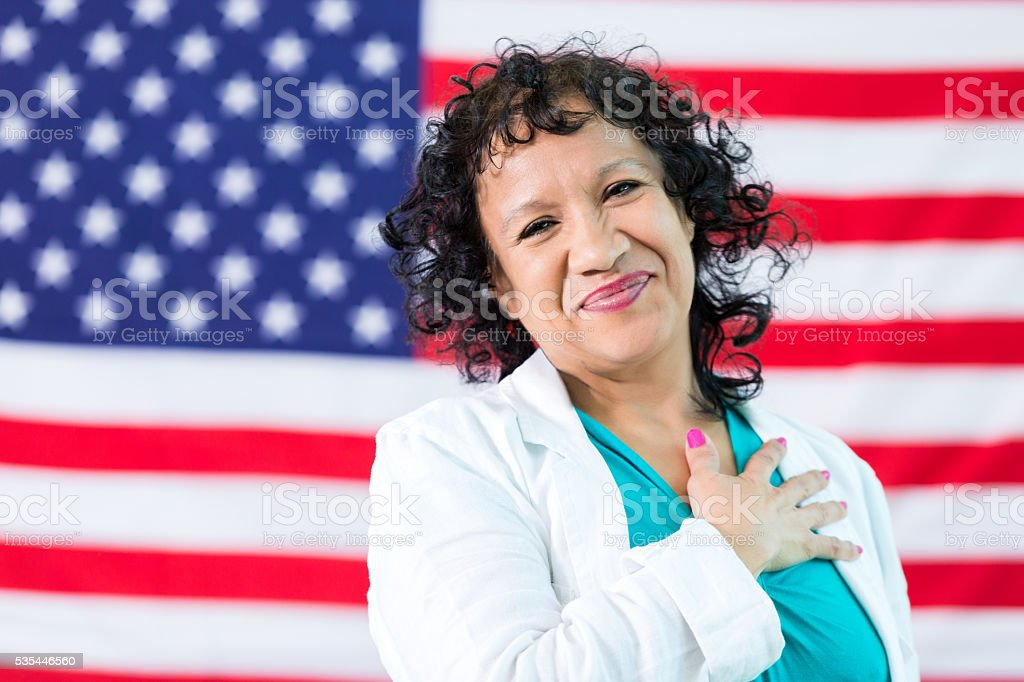 Hispanic Woman hand over heart stock photo
