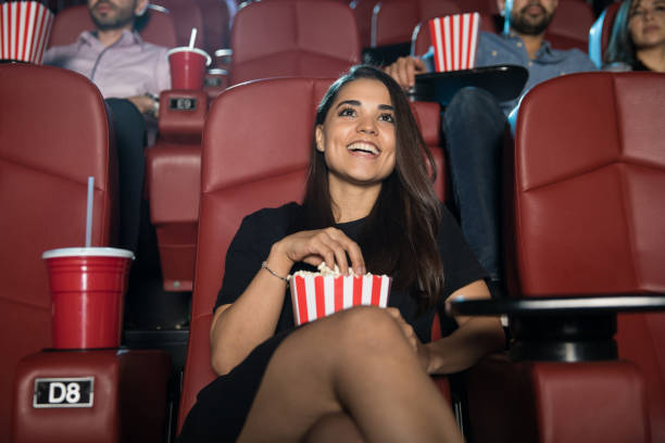 hispanic woman in a movie theater - film industry stock pictures, royalty-free photos & images