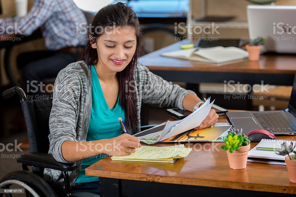 Hispanic woman in wheelchair in an office working on assignment – Foto
