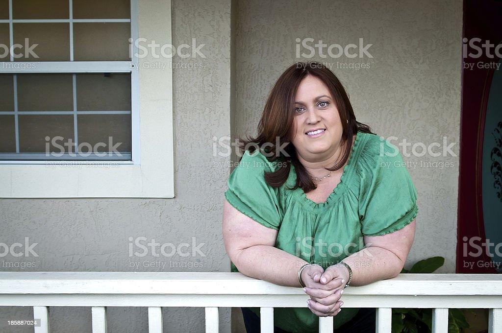 Hispanic woman leaning on her porch railing stock photo
