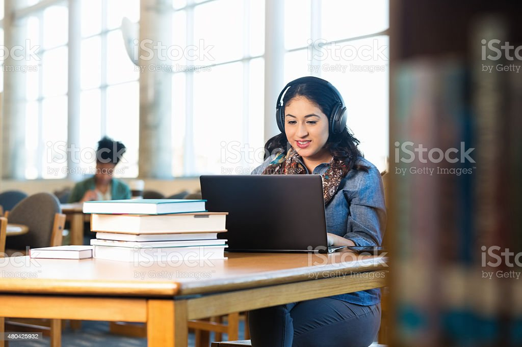 Hispanic woman listening to headphone while studying in college library stock photo