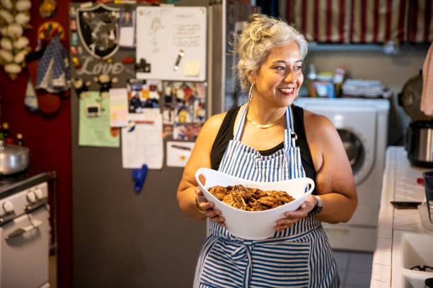 hispanic frau macht abendessen in küche - fett nährstoff stock-fotos und bilder