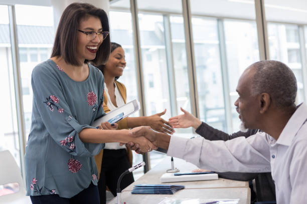 Hispanic woman meets her favorite speaker during meet and greet After the morning session of the small business expo, a Hispanic woman has the opportunity to shake hands with and talk to her favorite speaker. local government building stock pictures, royalty-free photos & images