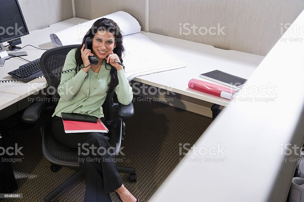 Hispanic woman on phone at office cubicle desk