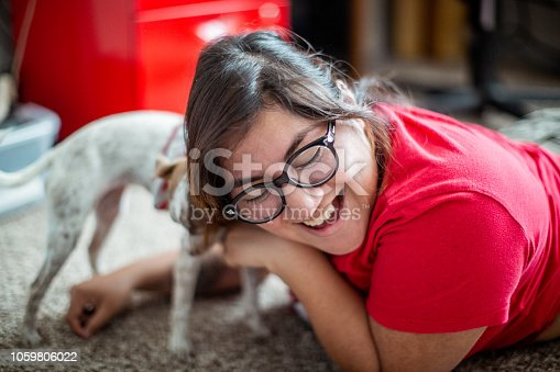 Lifestyle photo of a hispanic woman relaxing at home with her puppy dog. Shot indoors in their home using all natural light.