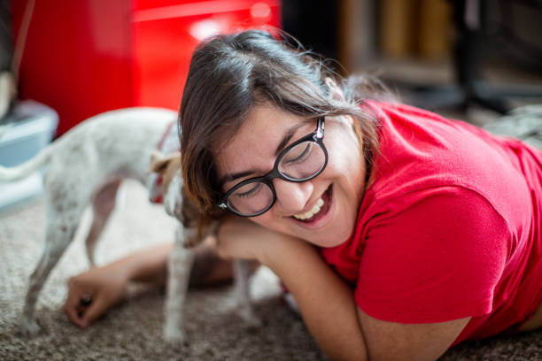 Hispanic Woman Playing at Home with Her dog Lifestyle photo of a hispanic woman relaxing at home with her puppy dog. Shot indoors in their home using all natural light. animal stage stock pictures, royalty-free photos & images