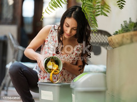A hispanic woman putting organic waste in a bin at home for a zero waste lifestyle.