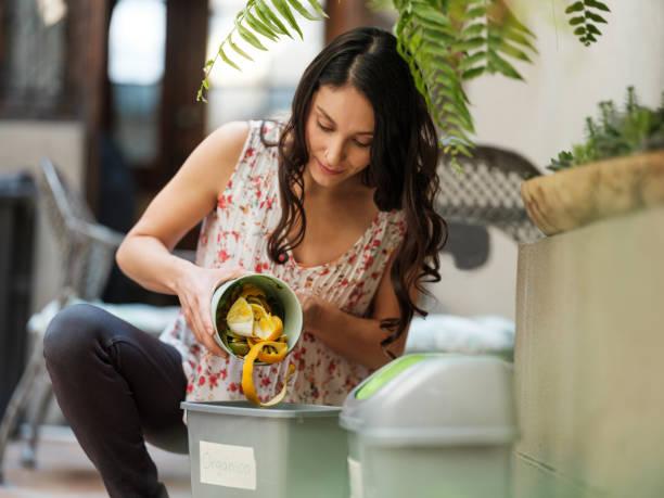 Hispanic woman putting organic waste in bin stock photo