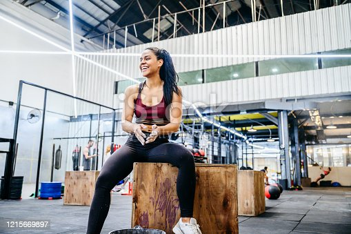 Female athlete in early 20s laughing and looking away from camera while sitting on jump box and rubbing chalk on hands before beginning weightlifting workout.