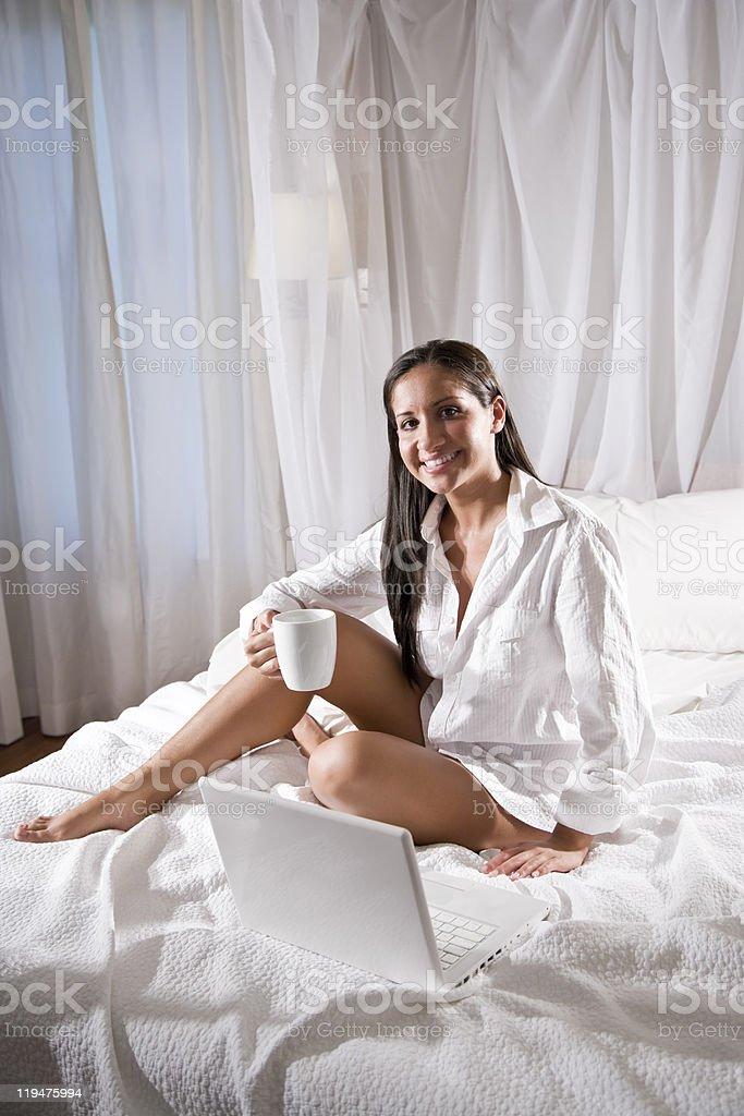 Hispanic woman sitting on bed drinking coffee royalty-free stock photo