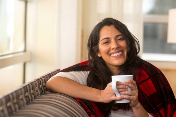 Hispanic woman sitting on the sofa smiling. stock photo