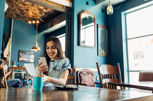 A hispanic woman of the Millennial Generation is taking a picture of a restaurant receipt after eating lunch at a local sushi restaurant. The woman is using her phone and bank's app to balance her monthly budget. Image taken in Utah, USA.