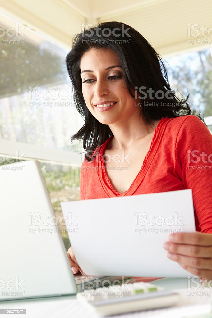 Hispanic Woman Using Laptop In Home Office royalty-free stock photo