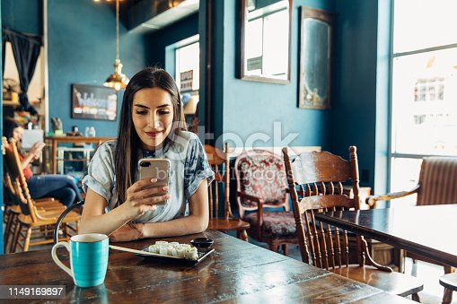 A Hispanic woman of the Millennial Generation is looking at her financial statement and showing a friend while eating lunch at a local sushi restaurant. She is using her bank's app to balance her monthly budget. Image taken in Utah, USA.
