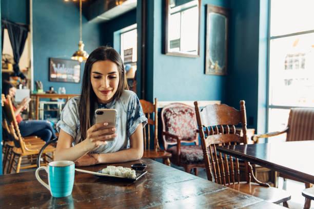 Hispanic Woman nutzt Telefon beim Mittagessen – Foto