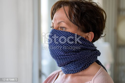 Hispanic woman wearing a blue face guard wrapped around her lower face as protection against the coronavirus or Covid-19 standing alongside a window in close up