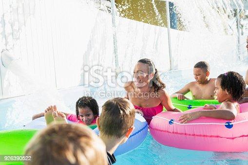 1091098220 istock photo Hispanic woman with children at water park 926390522