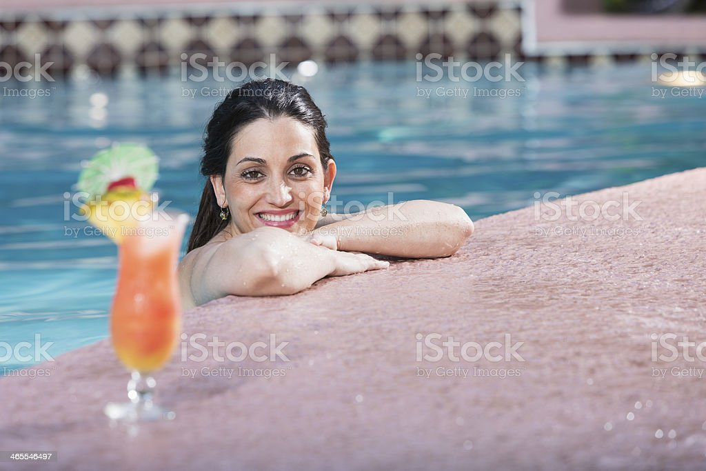 Hispanic woman with cocktail in swimming pool royalty-free stock photo
