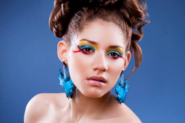 Hispanic woman with feather earrings stock photo