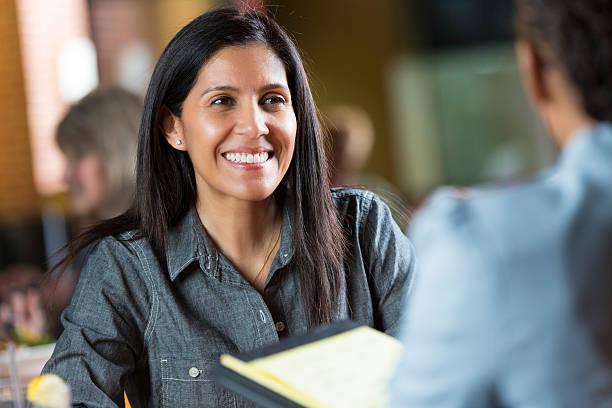 hispanic frau mit ihrem lebenslauf während der anwendung für job interview meeting - bewerbung lebenslauf stock-fotos und bilder