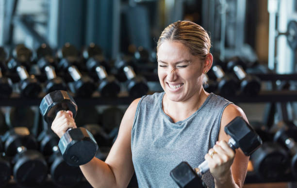 Hispanic woman working out at gym, lifting dumbbells A mid adult Hispanic woman in her 30s working out at the gym. She is an athlete with a muscular build sitting on a weight bench, lifting a dumbbells to strengthen her biceps. clenching teeth stock pictures, royalty-free photos & images