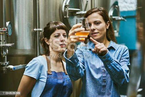 Close-up of Hispanic women in mid 30s working in craft beer brewery and checking sample for quality.