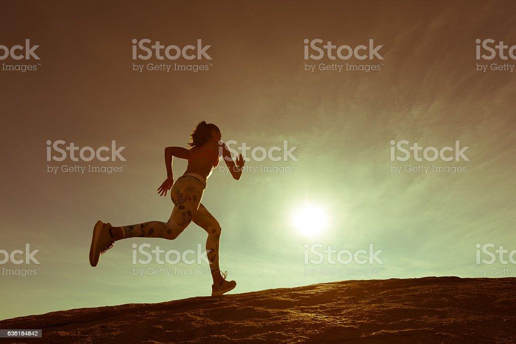 Hispanic Women Running Up A Granite Boulder - Photo
