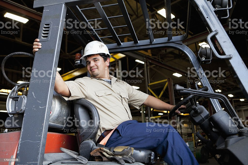Hispanic worker driving forklift stock photo
