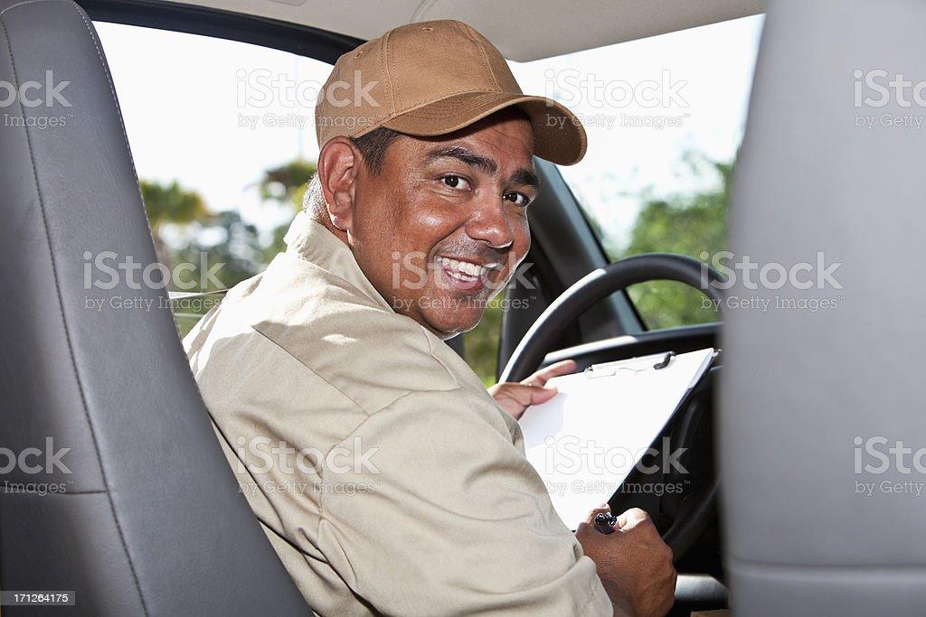 Hispanic worker driving van stock photo