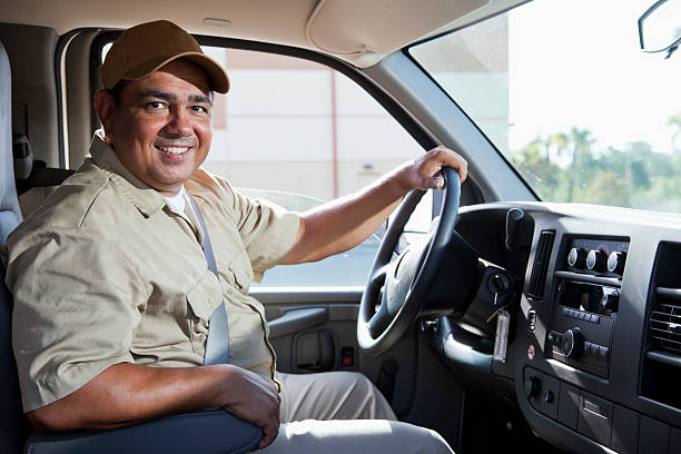 Hispanic worker driving van A Hispanic worker in his 40s wears a beige uniform and drives a commercial van.  The man is smiling and facing the camera, with his left hand on the steering wheel.  He is wearing a brown baseball cap, and trees and a building are in the background. driver occupation stock pictures, royalty-free photos & images