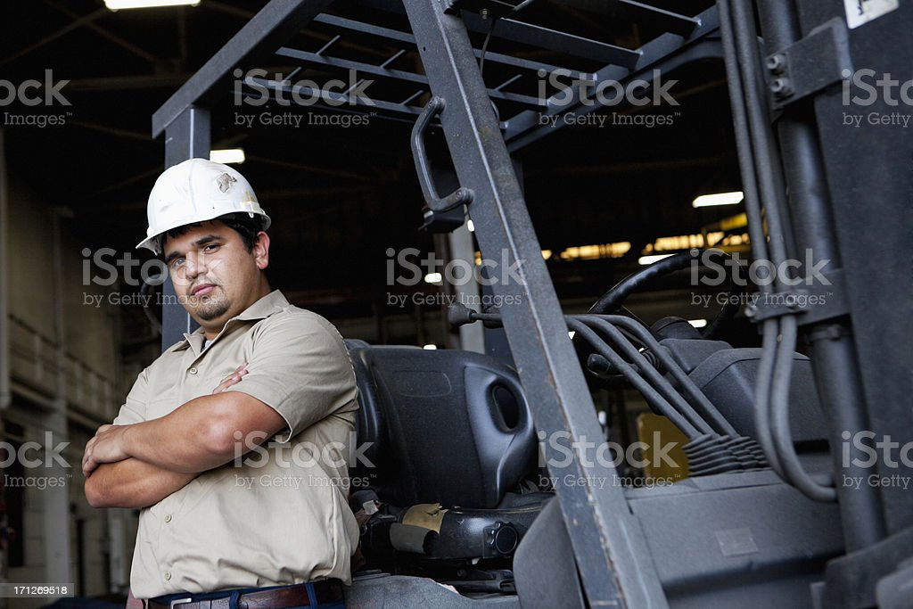 Hispanic worker standing in front of forklift stock photo