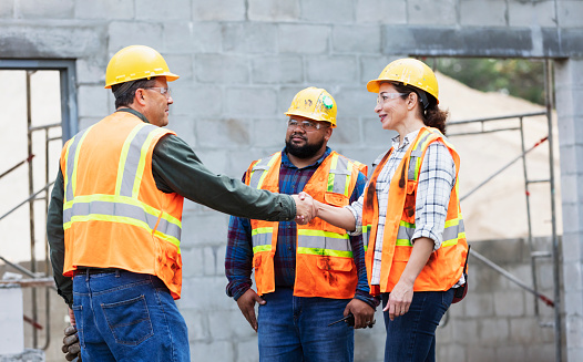 A multi-ethnic group of three workers at a construction site wearing hardhats, reflective vests and safety goggles, meeting and greeting. The woman and man shaking hands are Hispanic, in their 40s. Their coworker is mixed race African-American and Pacific Islander, in his 30s. He is standing beside the woman.