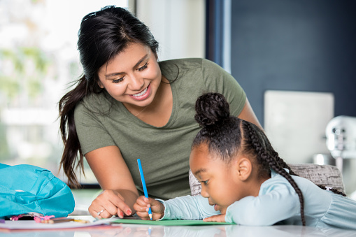 istock Hispanic young adult woman babysitting child and helping with homework 1057339834