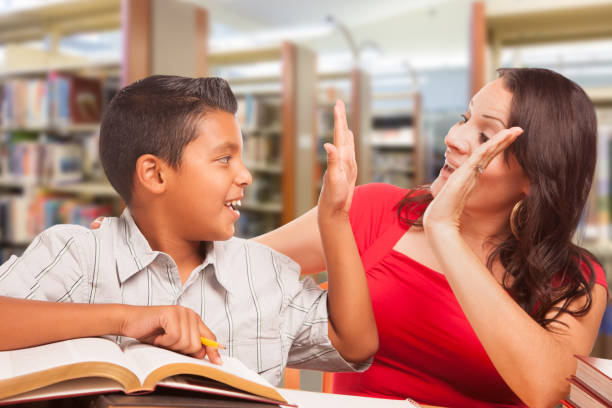Hispanic Young Boy and Famle Adult High Five Whilte Studying At Library Hispanic Young Boy and Famle Adult High Five Whilte Studying At Library. spanish and portuguese ethnicity stock pictures, royalty-free photos & images